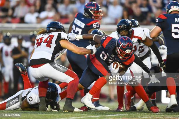 Running back William Stanback of the Montreal Alouettes runs the ball past defensive lineman JR Tavai of the Ottawa RedBlacks during the CFL game at...