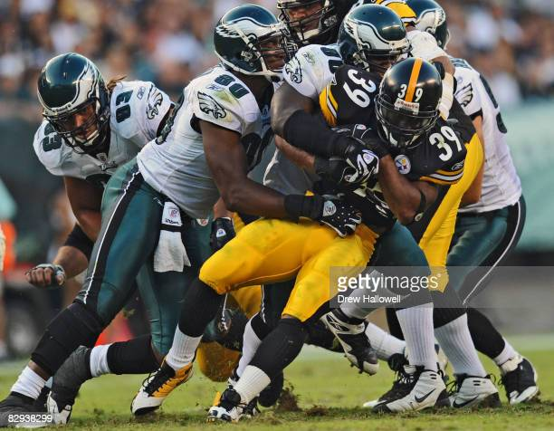 Running back Willie Parker of the Pittsburgh Steelers gets tackled by linebacker Omar Gaither and defensive end Darren Howard of the Philadelphia...