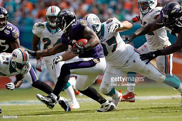 Running back Willis McGahee of the Baltimore Ravens breaks away from Defensive end Phillip Merling of the Miami Dolphins at Dolphin Stadium on...