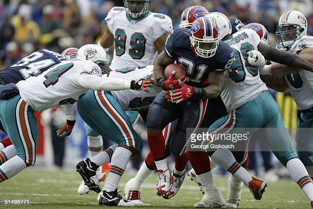 Running back Willis McGahee of the Buffalo Bills tries to elude Miami Dolphins defenders on October 17, 2004 at Ralph Wilson Stadium in Buffalo, New...