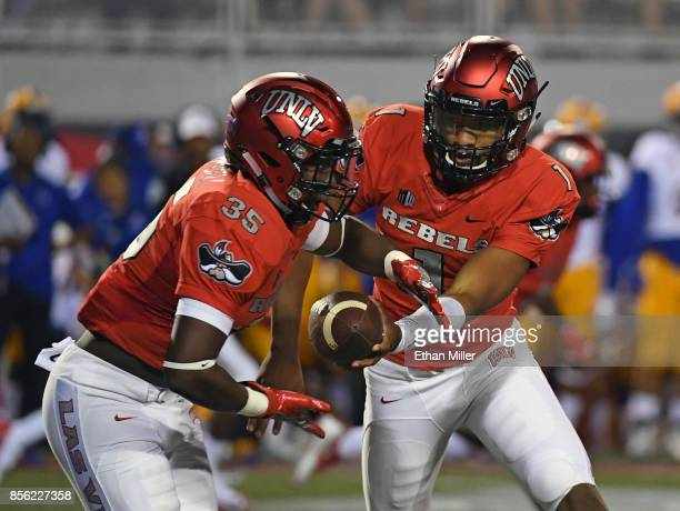 Running back Xzaviar Campbell of the UNLV Rebels takes a handoff from quarterback Armani Rogers during their game against the San Jose State Spartans...