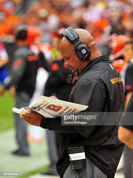 Running backs coach Hue Jackson of the Cincinnati Bengals looks at a notebook of plays on the sideline during a game against the Cleveland Browns on...