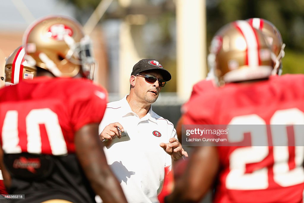 Running Backs coach Tom Rathman addresses players during a San Francisco 49ers practice session at Levi's Stadium on August 7, 2015 in Santa Clara, California.