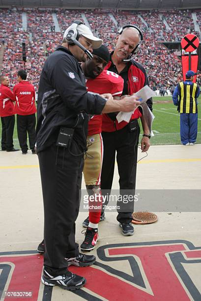 Running Backs Coach Tom Rathman and Tight Ends Coach Pete Hoener of the San Francisco 49ers talks with Brian Westbrook during the game against the...