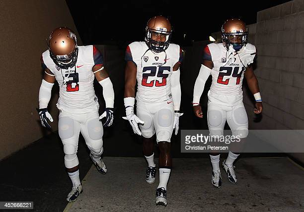 Running backs Kylan Butler Ka'Deem Carey and Terris JonesGrigsby of the Arizona Wildcats walk out to the field before the college football game...