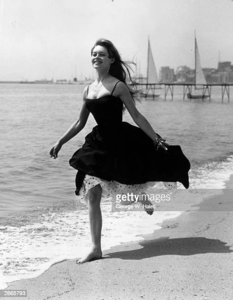 Running barefoot on the sands at Cannes, French film star, Brigitte Bardot .