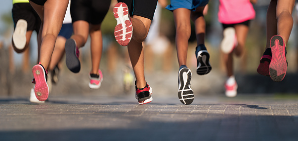 Running children, young athletes run in a kids run race,running on city road detail on legs 1030235128