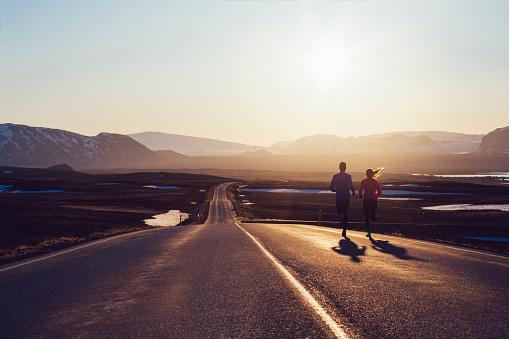 Running couple on road towards sunlit mountains - gettyimageskorea