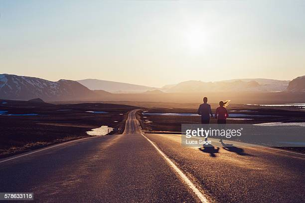 Running couple on road towards sunlit mountains
