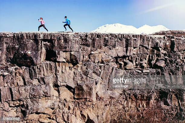 running couple run along rock edge with mountains - cliff stock pictures, royalty-free photos & images
