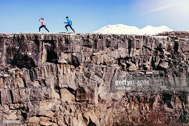 running couple run along rock edge with mountains - klippe stock-fotos und bilder