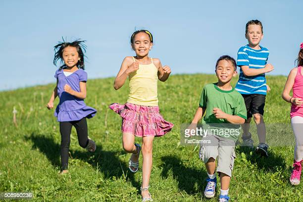 running down a hill together - kids playing tag stock photos and pictures