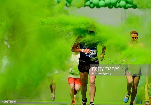 Running enthusiasts attend the marathon 5 km race through clouds of colorful powder thrown by volunteers during the Color Run 2014 at the Luzhniki...