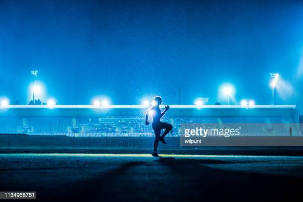 running exercising warming up young athlete in front of stadium floodlights blue - famous footballers silhouette stock pictures, royalty-free photos & images