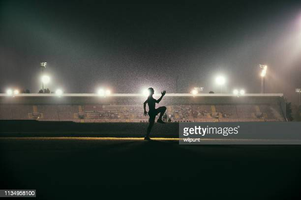 running exercising warming up young athlete in front of stadium floodlights - famous footballers silhouette stock pictures, royalty-free photos & images