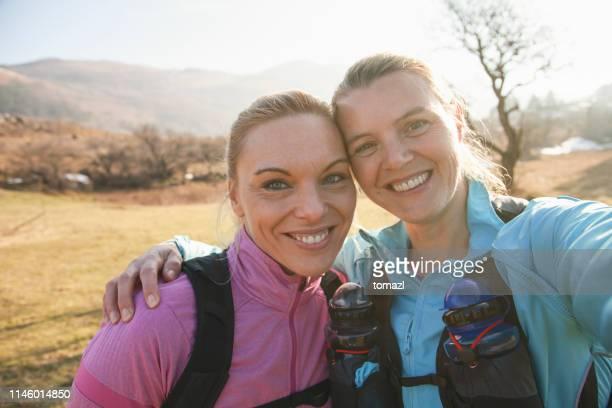 laufende freundinnen nehmen selfie - selbstporträt stock-fotos und bilder