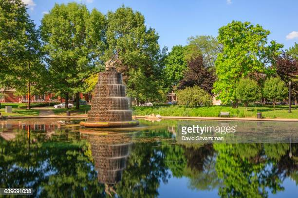 Running fountain in Goodale Park, Columbus Ohio reflects in the pond