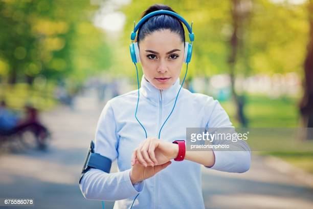 Running girl is checking her smart watch