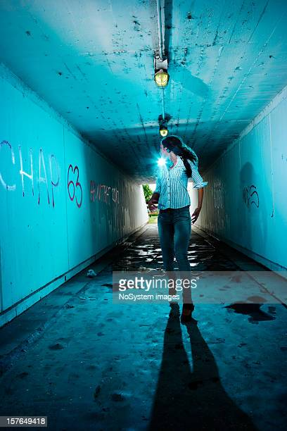 Running girl looking backwards in tunnel