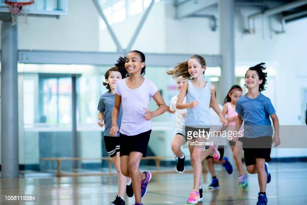 running in the gym - childhood stock pictures, royalty-free photos & images