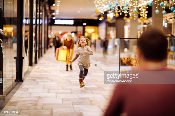running into dads arms - shopping centre stock photos and pictures
