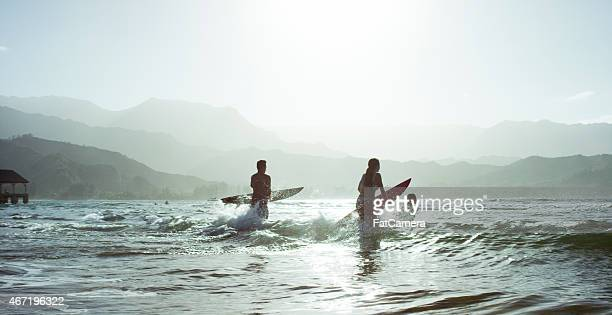Running into the Ocean with Surfboards