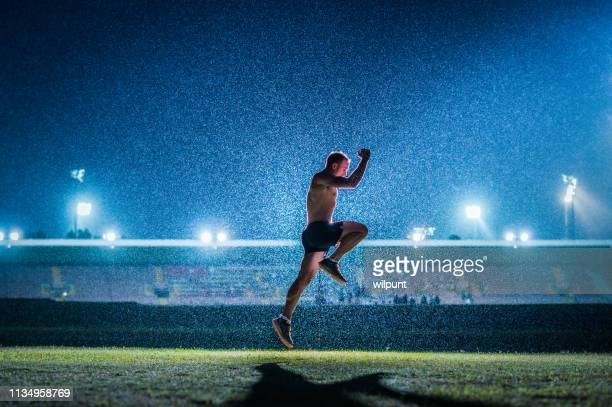 running jumping warming up young athlete success in front of stadium floodlights - famous footballers silhouette stock pictures, royalty-free photos & images