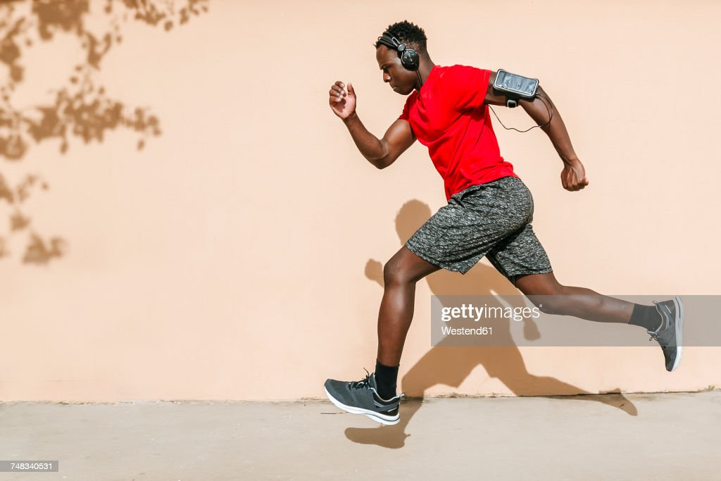 Running man listening music with headphones : Stock Photo