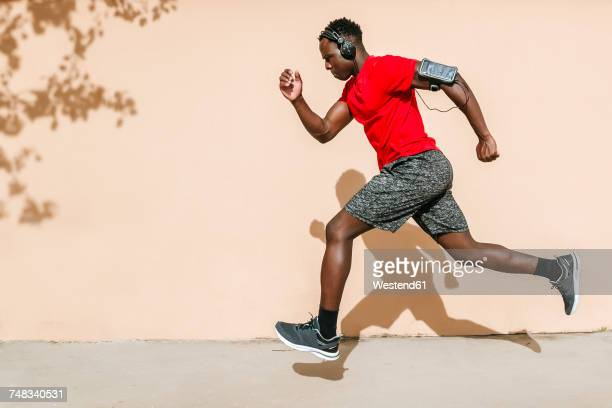 Running man listening music with headphones