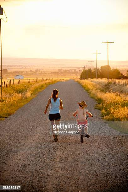 running mom with boy on bike, country road