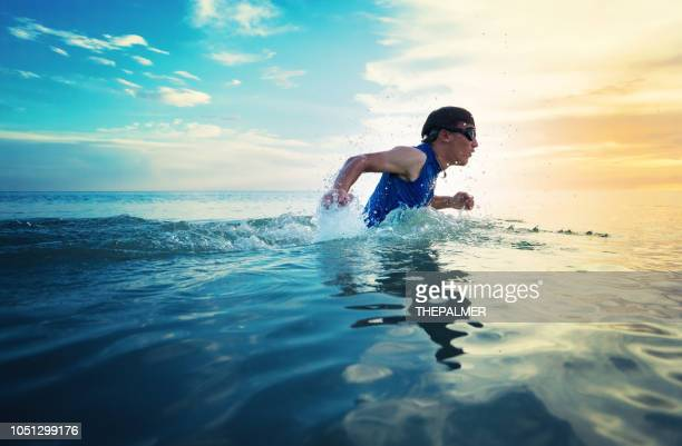 running on the beach at sunset - triathlon stock pictures, royalty-free photos & images