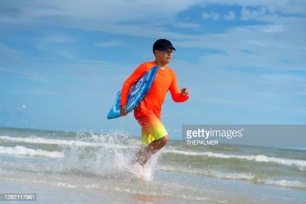 running on the beach holding a skimboard - fort myers stock pictures, royalty-free photos & images