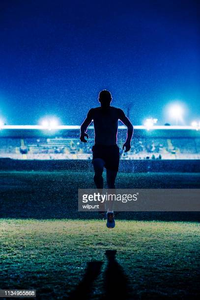 running on the spot warming up getting ready for competition in the rain at night - famous footballers silhouette stock pictures, royalty-free photos & images