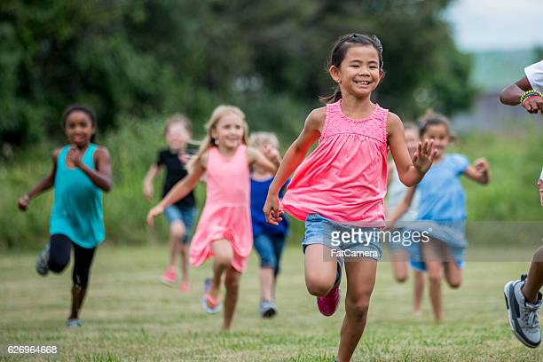 running outside during recess - kids playing tag stock photos and pictures