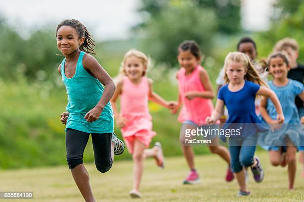 running outside on a sunny day - kids playing tag stock photos and pictures