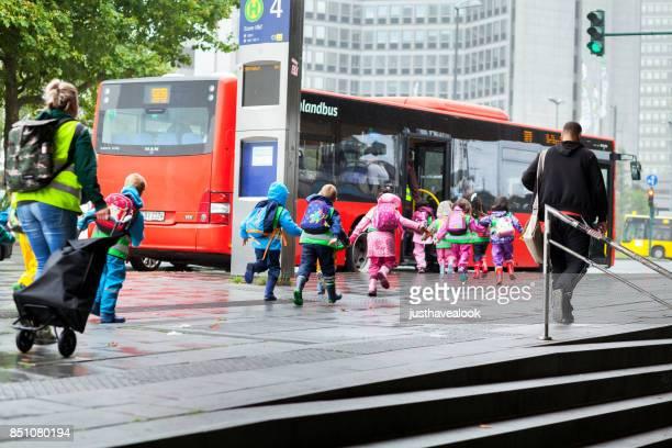 Kinder im Vorschulalter laufen an Bushaltestelle