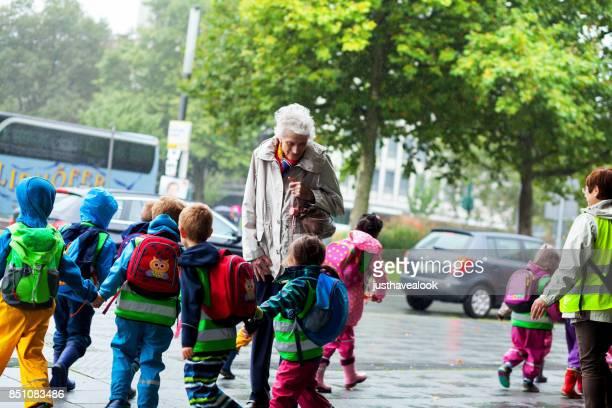 Running preschool kids surrounding old senior woman