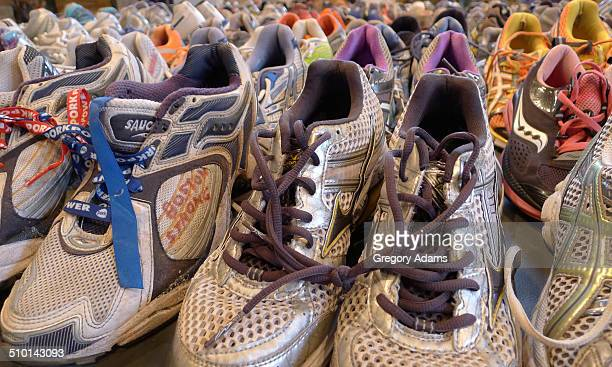 """Running shoe memorial to the victims of the 2013 Boston Marathon bombing. The words """"Boston Strong"""" are written on the side of one of the shoes."""