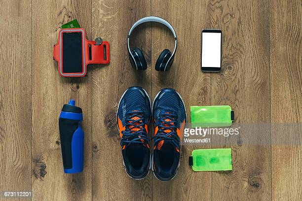 Running shoes, headphones, drinking bottle, smartphone and bags