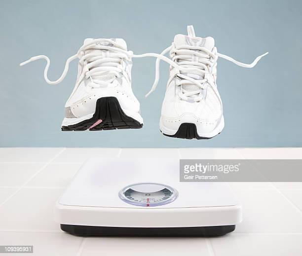 running shoes hovering above bathroom scale - en l'air photos et images de collection
