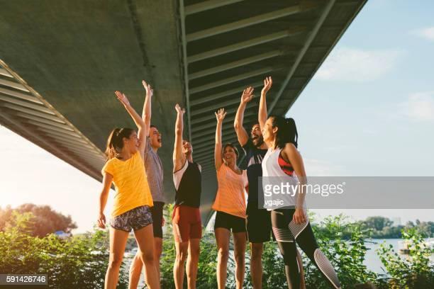 equipo corriendo uniendo manos. - grupo mediano de personas fotografías e imágenes de stock