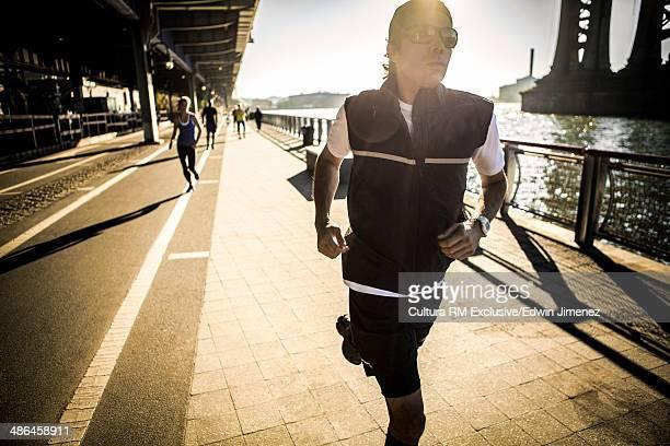 Running team, running along waterfront, New York, USA