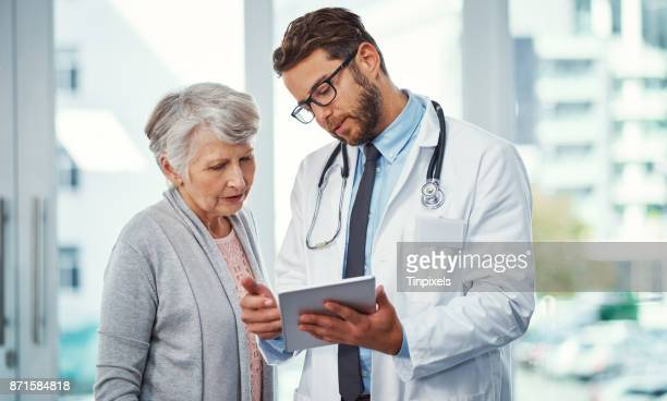 running through a treatment plan with a patient - doctor stock pictures, royalty-free photos & images