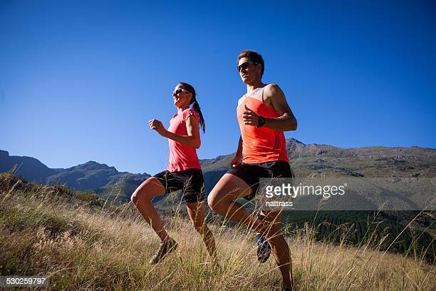 running together up a mountain trail - striding stock pictures, royalty-free photos & images