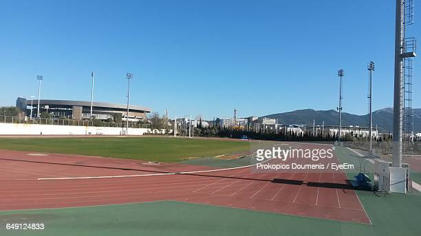 running track in stadium against clear blue sky - track and field stadium stock pictures, royalty-free photos & images