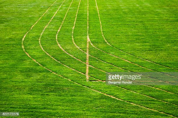 running track lanes on grass field - length stock pictures, royalty-free photos & images