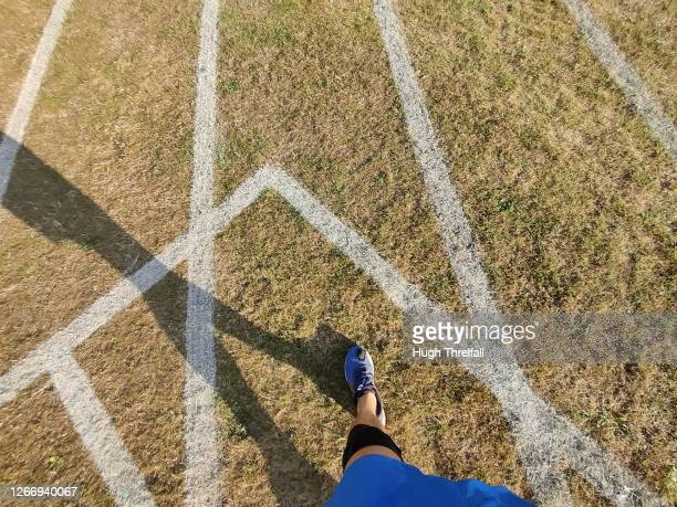 running track with white painted lines and runners shadow. - hugh threlfall stock pictures, royalty-free photos & images
