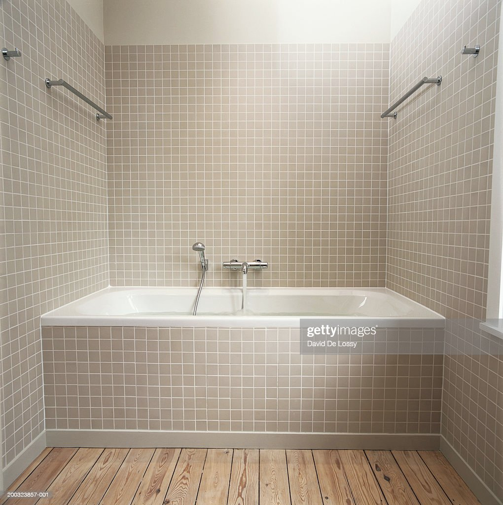 Running water flowing from faucet into bathtub : Stock Photo