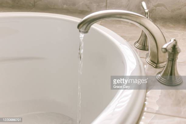 running water from bathtub faucet - flowing water stock pictures, royalty-free photos & images