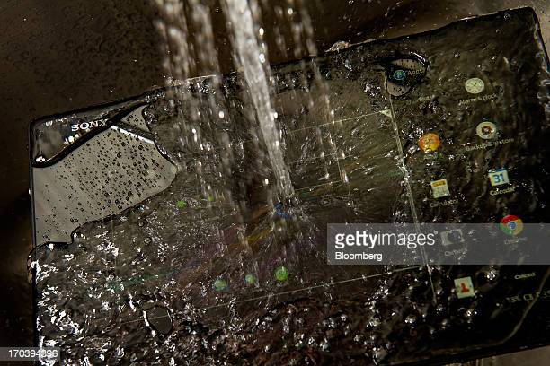 Running water pours over the Sony Corp Xperia Tablet Z in San Francisco California US on Tuesday June 11 2013 The ultrathin waterproof Sony Xperia...